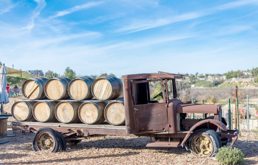 Old Rusty Vintage truck on display at vineyard with wooden wine barrels on top in Temecula