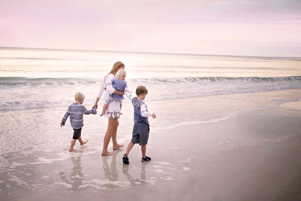 Mother and her young children walking along the shore of Marco Island