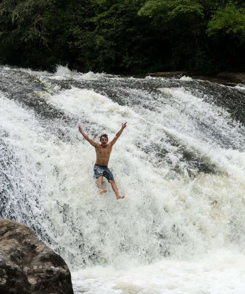 A young man slides down the rock in Turtleback Falls