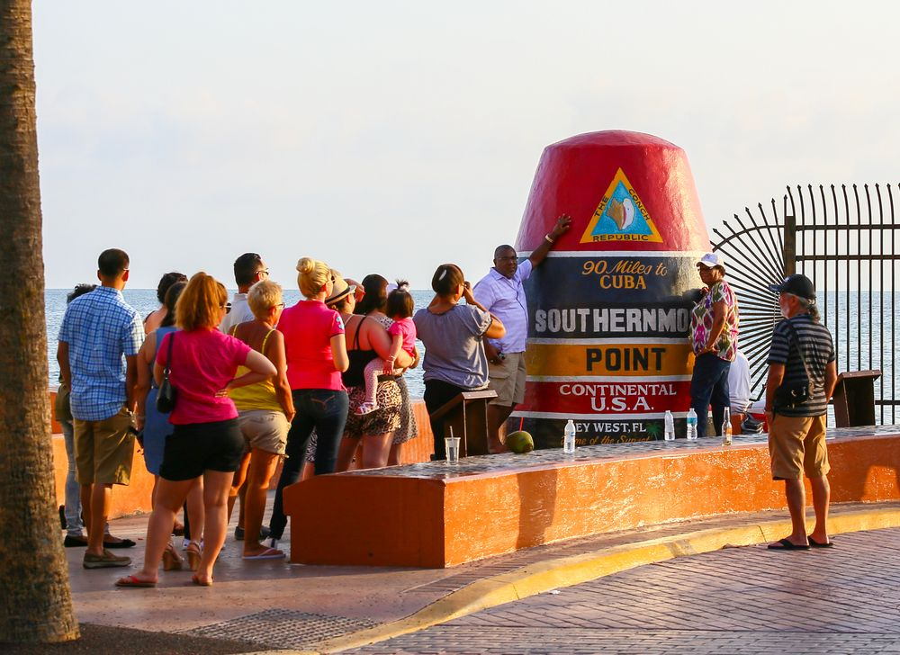 People Taking Picture With the Southernmost Point Marker in Key West in Sunset