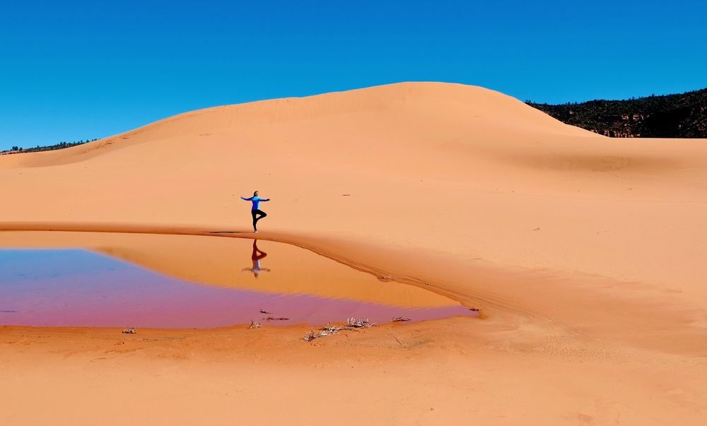 A woman doing yoga in Coral Pink Sand Dunes State Park