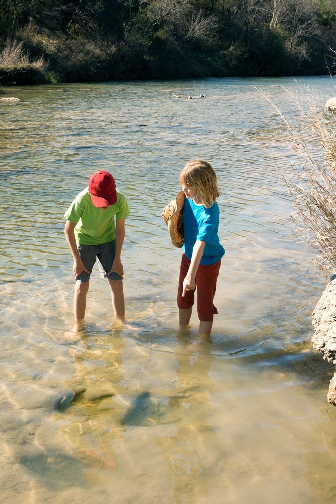 Children looking at fossilized dinosaur tracks at Dinosaur Valley State Park